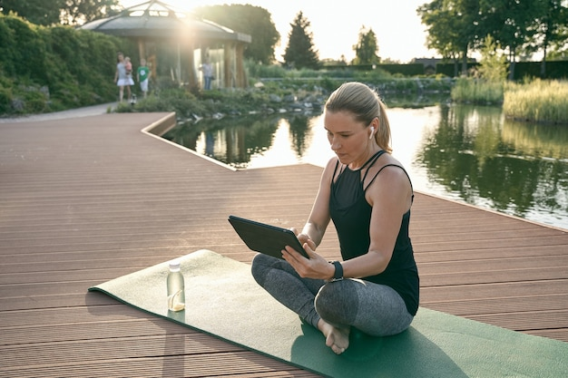 Sporty beautiful woman watching tutorial on a tablet pc while doing yoga on a mat in nature on a