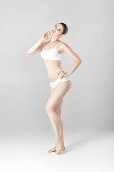 Sporty beautiful woman with a perfect body in white lingerie on a gray