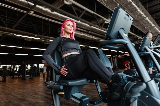 ファッショナブルな黒のスポーツウェアのピンクの髪を持つスポーティな美しい若いフィットネスモデルの女性は、ジムでエアロバイクに座って訓練します