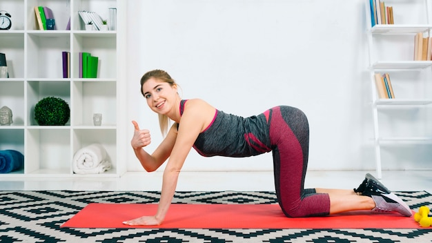 Sporty beautiful young woman doing backbend in cow posture showing thumb sign