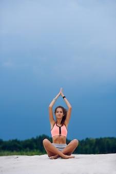 スポーティな美しい若い女性はヨガを練習し、簡単な気持が良いポーズで座っています。ビーチでの瞑想。
