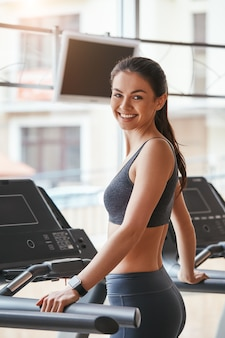 Sporty beauty cheerful and beautiful young woman in sportswear is standing on treadmill at gym
