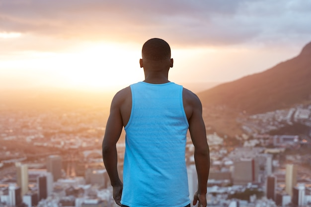 강한 근육질의 몸매를 가진 스포티 한 흑인 남성은 뒤로 물러서 고 자연 경관, 산과 도시에 감탄하면서 일출과 함께 하늘을 바라보고 있습니다. 스포츠맨은 자유를 즐긴다