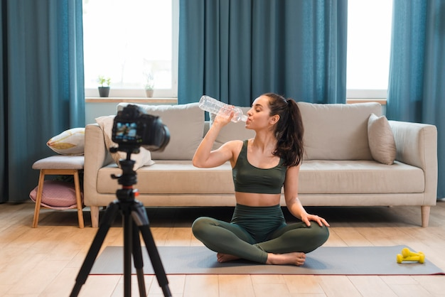 Sporty blogger sitting in lotus position drinking water