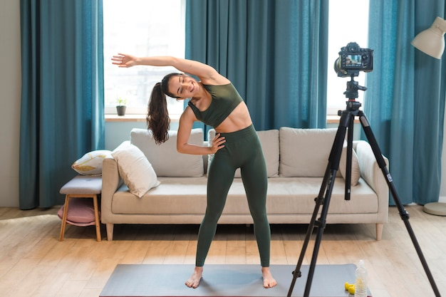 Sporty blogger stretching in front of camera
