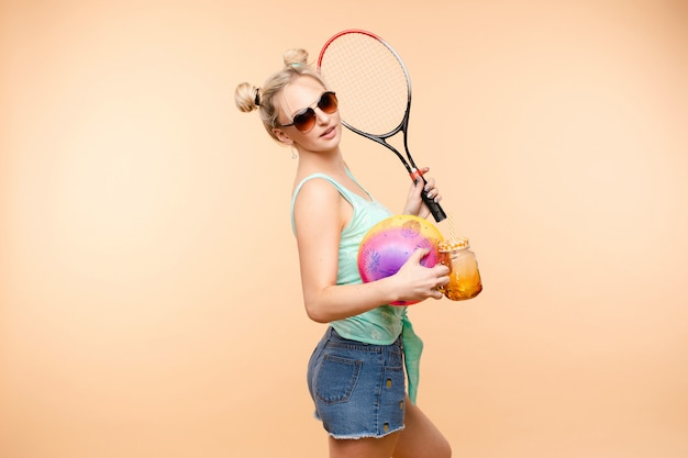 Sporty blonde drinking fresh juice and doing sport