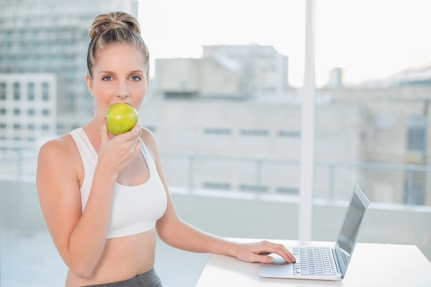 Sporty blonde eating apple while using laptop