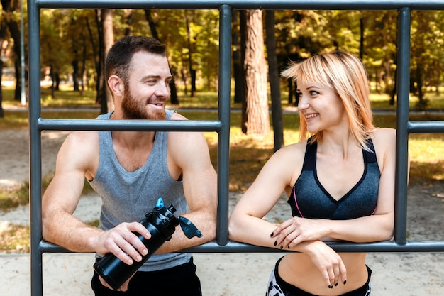 Sporty blonde girl and bearded man is resting after workout training in a park at autumn day.