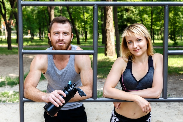 Sporty blonde girl and bearded man is resting after workout training in a park outdoor.