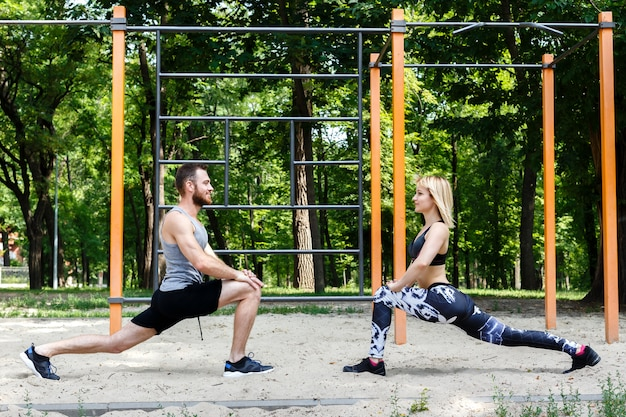 Sporty blonde girl and bearded man is warming up before training in a park outdoor.