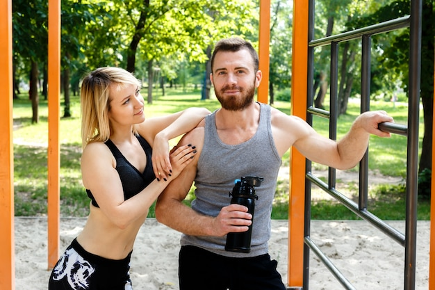 Sporty blonde girl and bearded man resting after workout training in a park outdoor. man holding a black bottle with water.