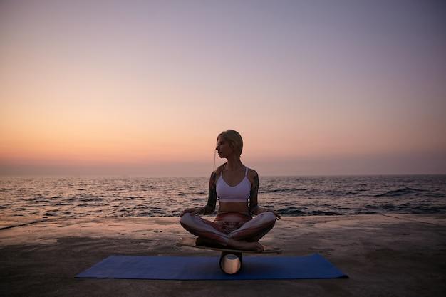 Donna bionda sportiva con acconciatura casual in abbigliamento sportivo in posa sulla vista mare durante l'alba, seduto sulla tavola di equilibrio con le gambe incrociate e guardando da parte