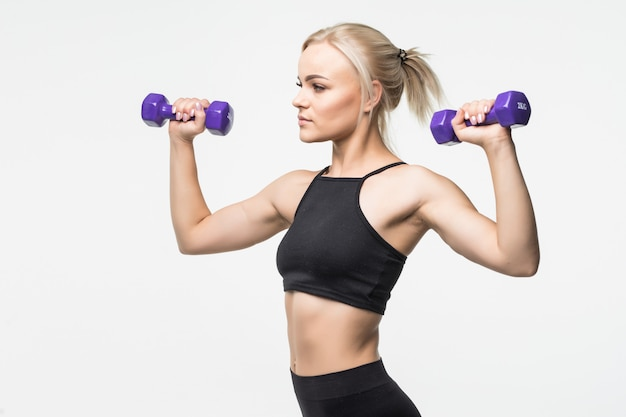 Sporty blonde young girl with fit muscular body works with dumbbells in studio on white
