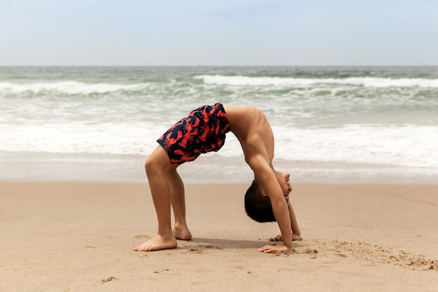 Sporty boy doing wheel pose on the beach, yoga practice in the morning outdoor