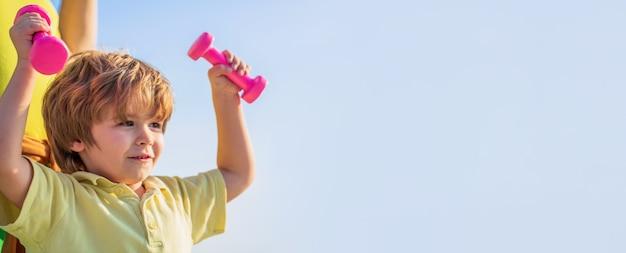 ダンベルを持つスポーティな男の子。スポーツ。フィットネス、健康、エネルギー。健康的な生活様式。元気な男の子はダンベルで運動をします。フィットネスの子供。ダンベルで運動する子供。小さな子供のためのスポーツ。