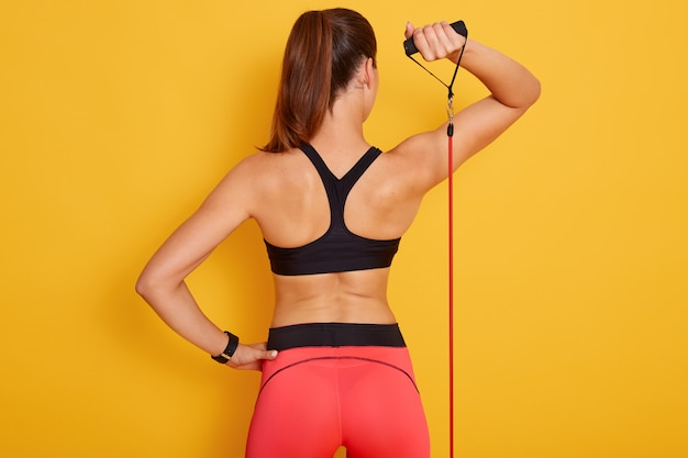 Sporty brunette female with ponitail standing backwards, working out with expander for back muscles and arms, fitness model isolated