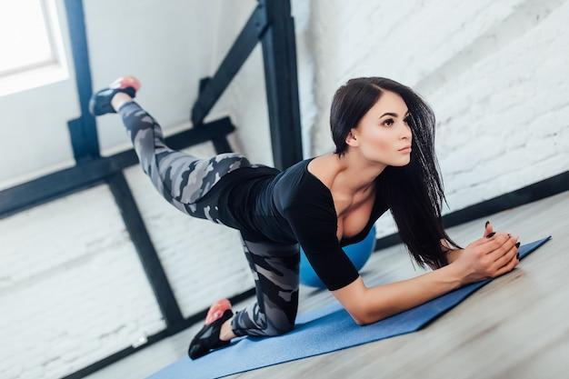 Спортивная женщина брюнет делает упражнения в белой комнате, девушка имеет время йоги.