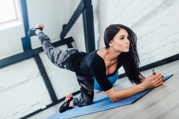 Sporty brunette woman doing exercisses at white room, girl have a yoga time.
