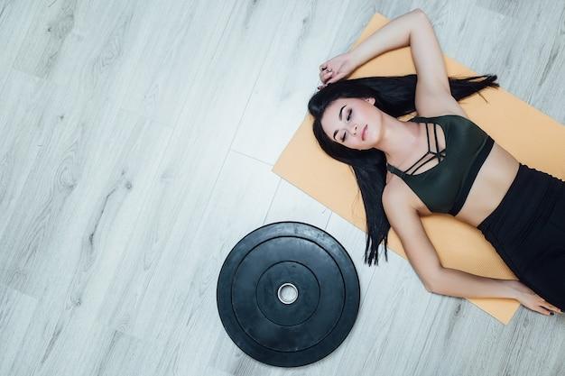 スポーツ用品と灰色の床に横たわってスポーティなブルネットの女性