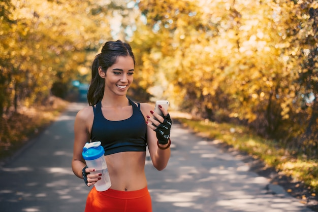Sporty brunette woman using smart phone after running.
