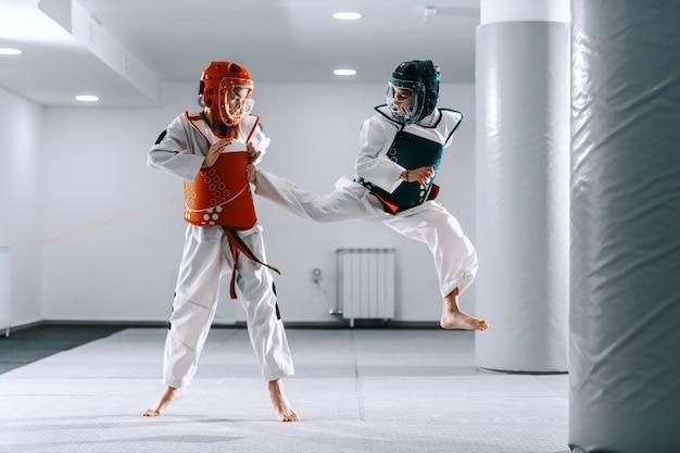 Sporty caucasian boys having taekwondo training in white gym. one boy kicking other.