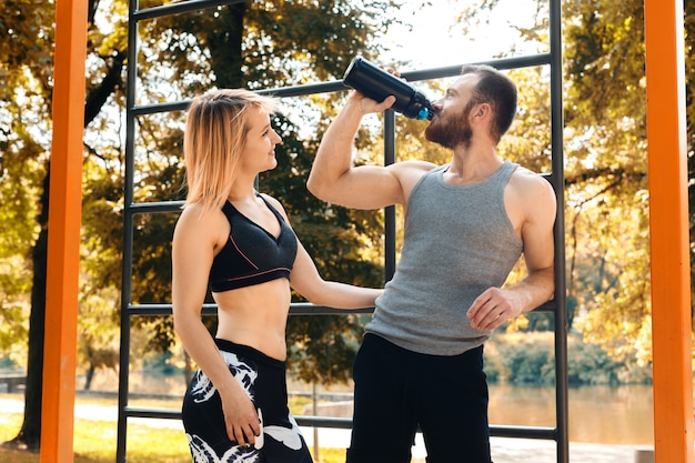Sporty caucasian couple is resting after workout training in a park at autumn day. man drinking water from a black bottle.