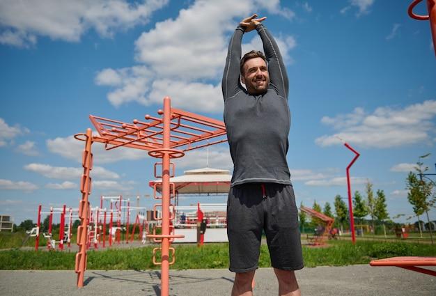 屋外でワークアウトするスポーティな白人ヨーロッパ人。屋外でフィットネストレーニングを楽しんだり、腕を上げたり、ストレッチやストレッチをしたりする幸せなスポーツマン。