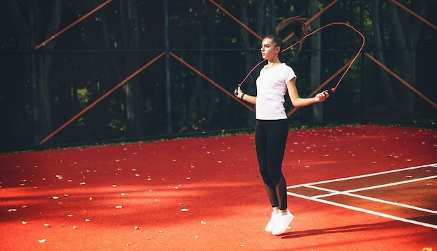 晴れた夏の朝に赤いテニススタジアムで縄跳びを使用してスポーティな白人の女の子