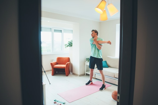 Sporty caucasian man warming up in front of camera having online gym session