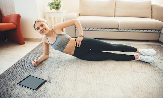 スポーツウェアのスポーティな白人女性は、カメラに微笑んでタブレットを使用して床に横板張りです