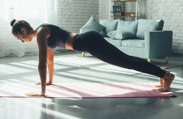 Sporty caucasian woman is doing pushups at home on a yoga mat wearing sportswear