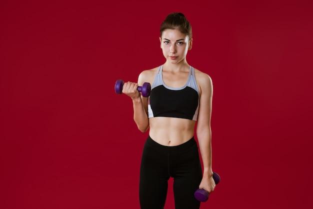 빨간 벽에 그녀의 손에 아령과 운동복에 스포티 한 백인 젊은 여자는 스포츠에 들어간다