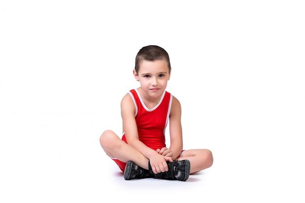 Спортивный веселый мальчик в синих борцовских колготках готов заниматься спортивными упражнениями