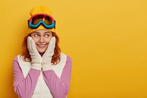 Спортивный веселый отдыхающий отдыхает в горах, трогает щеки руками, одетыми в варежки, использует маску для сноуборда, имеет счастливое выражение лица, стоит на желтом фоне