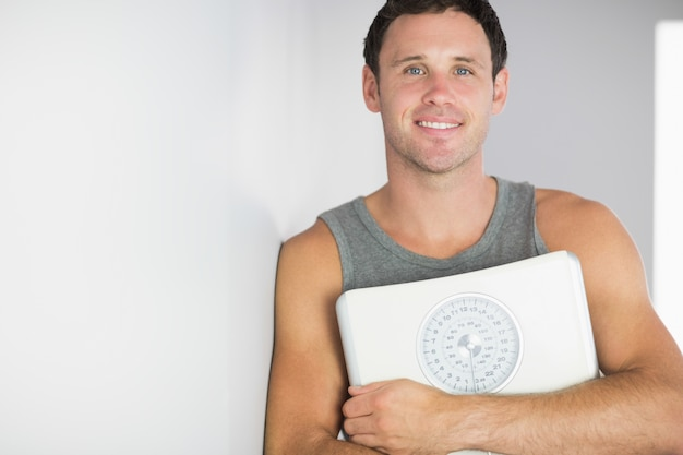Sporty cheerful man leaning against wall holding a scale