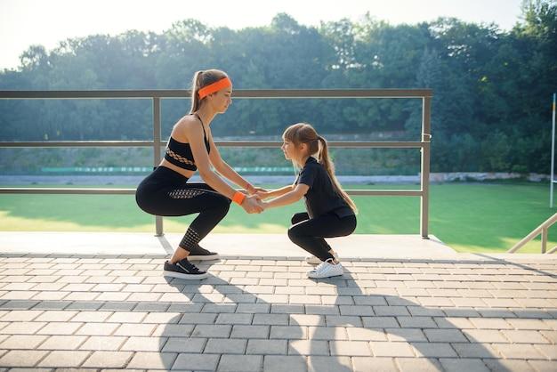 야외 경기장에서 피트니스 운동을하는 동안 점프 운동을하는 스포티 한 커플