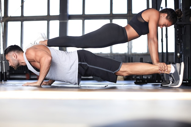 Sporty couple doing plank exercise in gym.