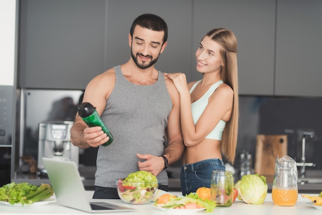 Sporty couple on kitchen. vegetables cocktail.
