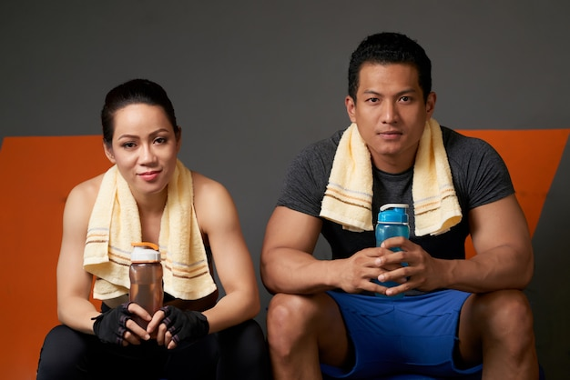 Sporty couple looking at camera seated on the couch after the training session