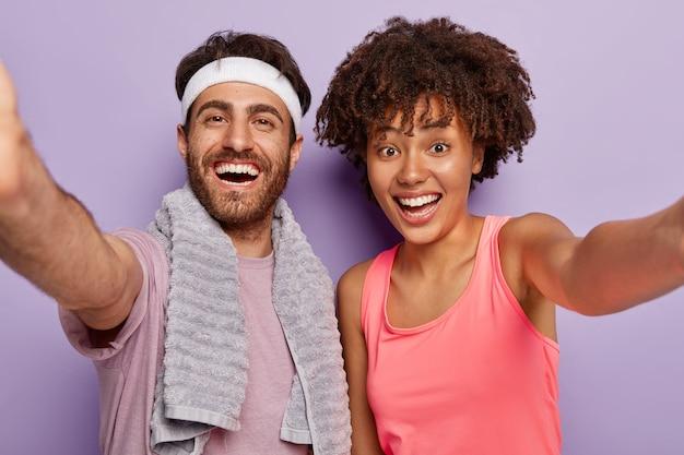 Спортивная пара делает селфи после фитнеса, широко улыбается, выражает хорошие эмоции, носит повседневную одежду, держит руки вытянутыми, ведет здоровый образ жизни, изолирована за фиолетовой стеной. тренировка, тренировка