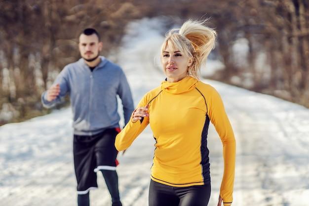 눈 덮인 겨울 날 숲에서 경주하는 스포티 한 커플. 건강한 습관, 마라톤, 겨울 피트니스