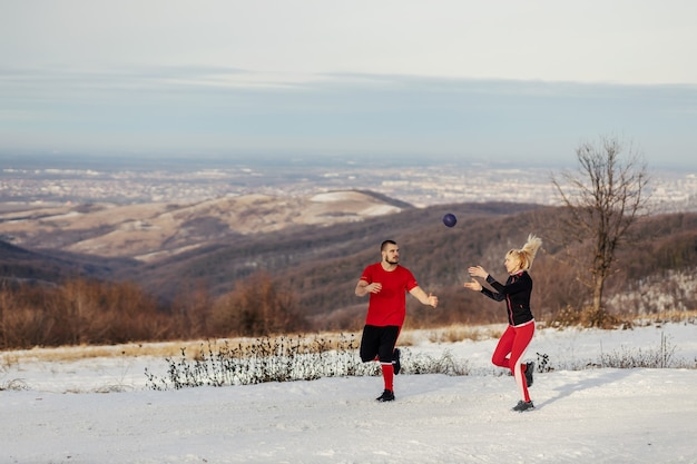 派手な冬の日に自然の中で走り、フィットネスボールでエクササイズをしているスポーティなカップル。冬のフィットネス、健康的な習慣、関係