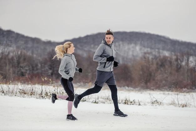 눈 덮인 겨울 날 자연 속에서 함께 달리는 스포티한 커플. 건강한 생활, 겨울 피트니스, 유산소 운동