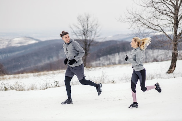 겨울에 눈에 자연에서 함께 실행 하는 스포티 한 커플. 관계, 건강한 습관, 겨울 피트니스