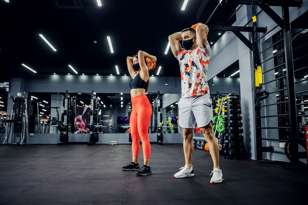 Sporty couple in shape with face masks standing in gym and lifting weights. h