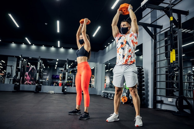 Sporty couple in shape with face masks standing in gym and lifting weights.