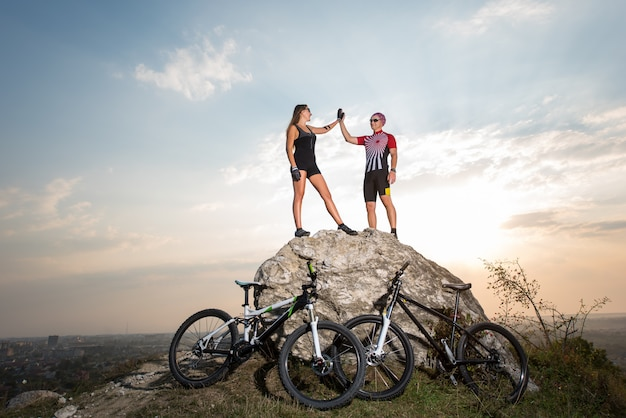 Sporty cyclist couple standing on a rock and touches the hand to hand against blue sky