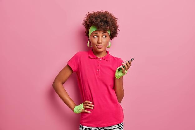 스포티 한 어두운 피부의 곱슬 머리 여자는 허리에 손을 얹고, 휴대 전화를 손에 들고, 온라인 교육을 위해 특수 응용 프로그램을 사용하고, 머리띠, 스포츠 장갑, 분홍색 티셔츠를 착용합니다.