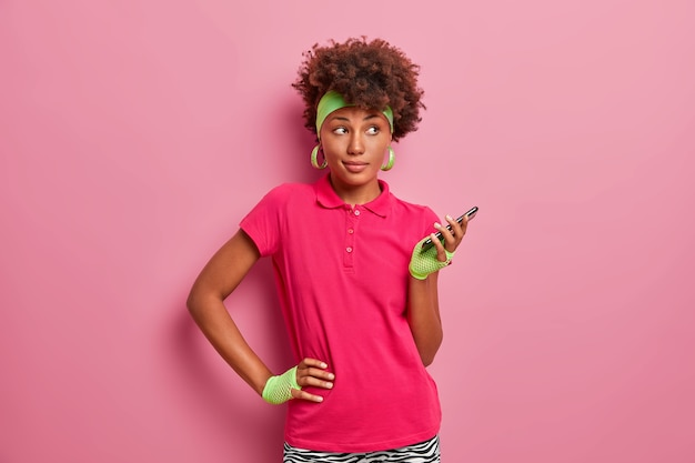 Sporty dark skinned curly haired woman keeps hand on waist, holds mobile phone in hand, uses special application for training online, wears headband, sport gloves, pink t shirt