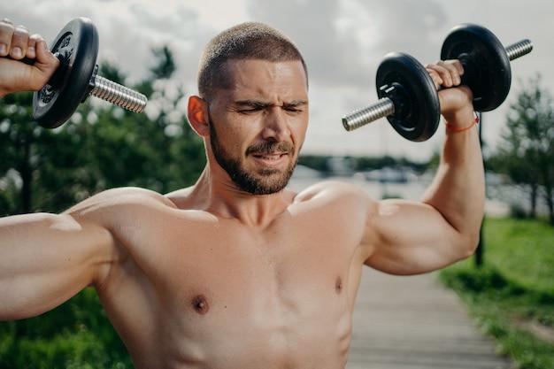Спортивный решительный мускулистый европейский мужчина делает упражнения с гантелями